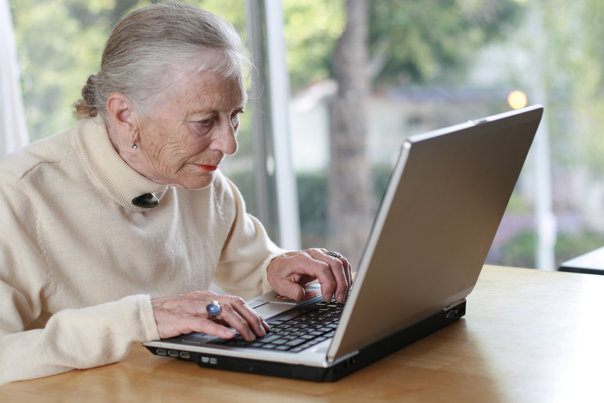 Elderly lady typing on lapto