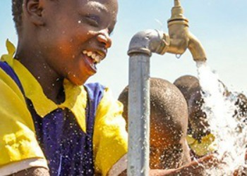 African child and water faucet