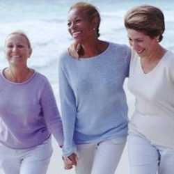 older women friends walking on beach