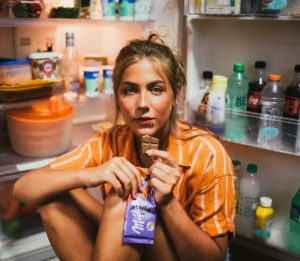 woman eating at open refrigerator